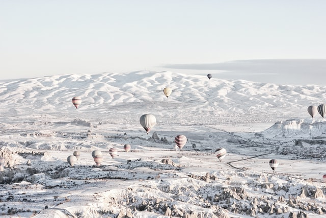 Snow covered ground with white air balloons hovering